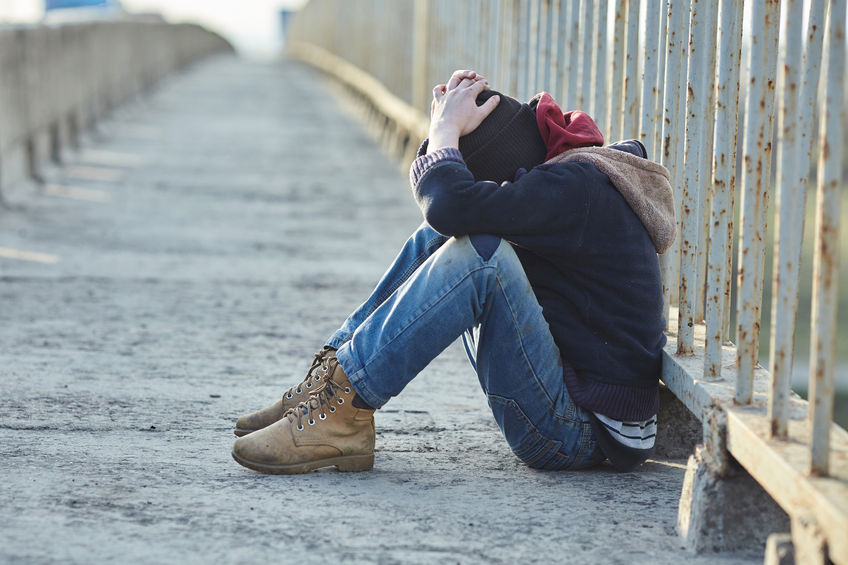 A young person sitting on a bridge, excluded from community.