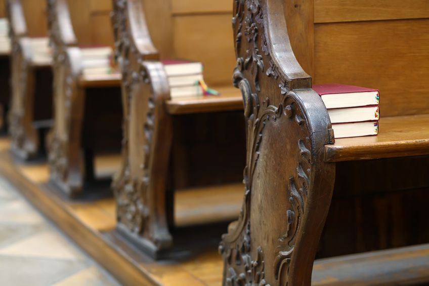 Hymnal books in pews for a worship service.