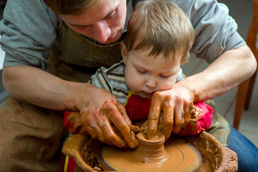 A dad helping his toddler at a pottery wheel, shaping the clay and their relationship.