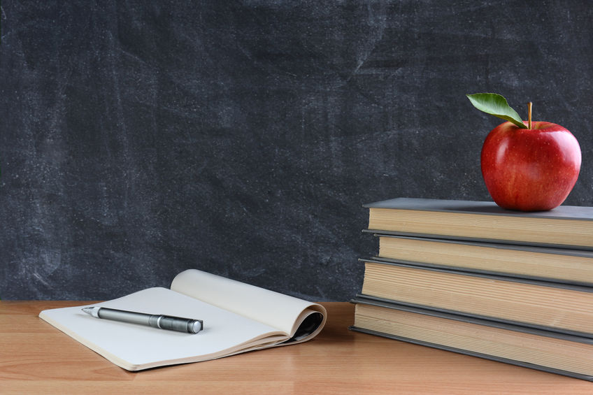 The desk of a teacher with books and an apple.