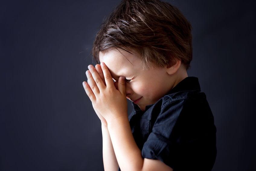 A sad boy praying.
