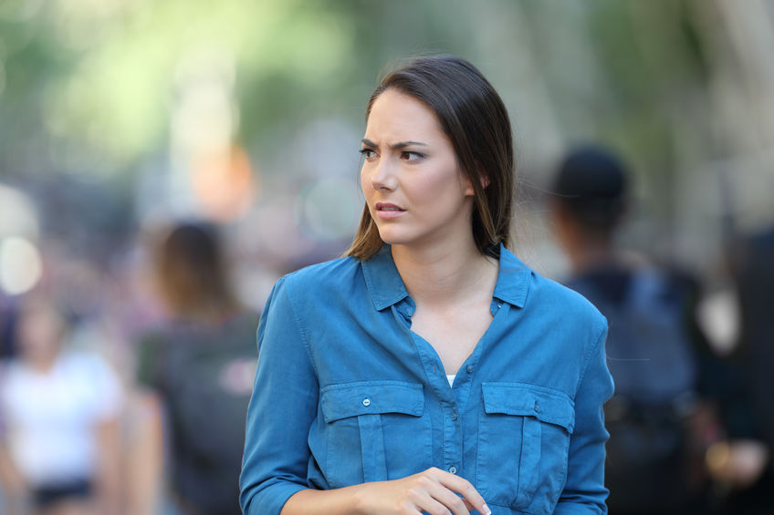 Anxious woman walking on the street looking to the side