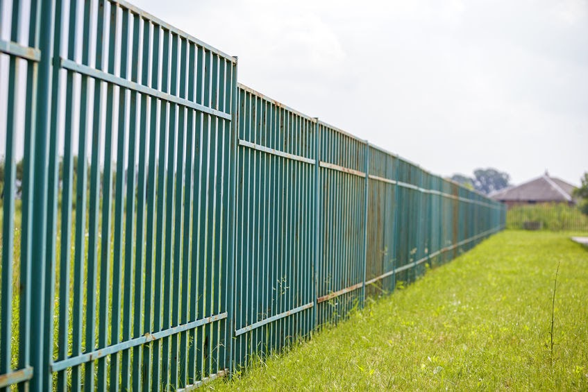 A blue metal fence keep outsiders and insiders separate.