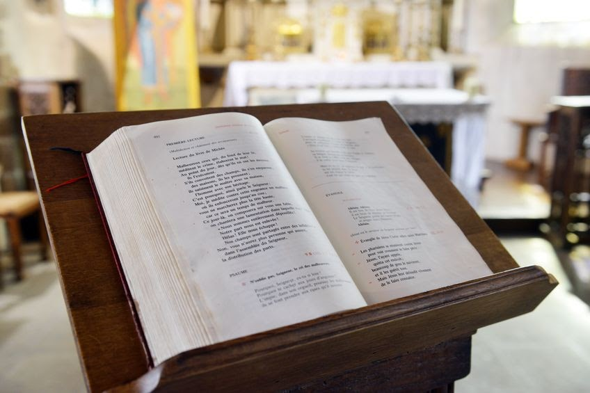 A hymnal or liturgy book on a lectern at church.