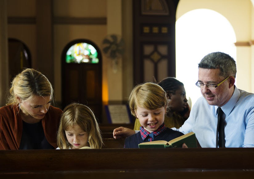 A family in worship teaching kids the language of faith.
