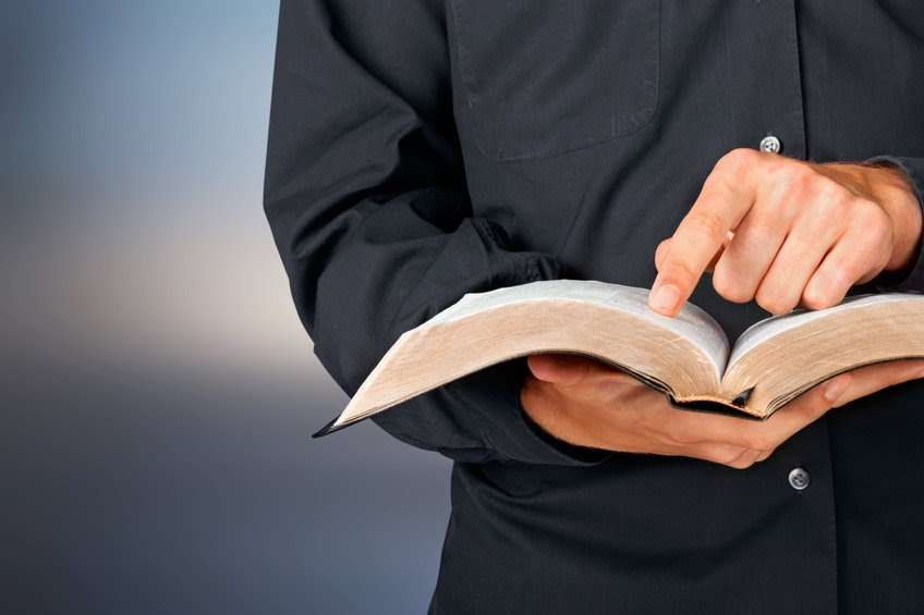 A pastor holding an open Bible. Preaching sermons.
