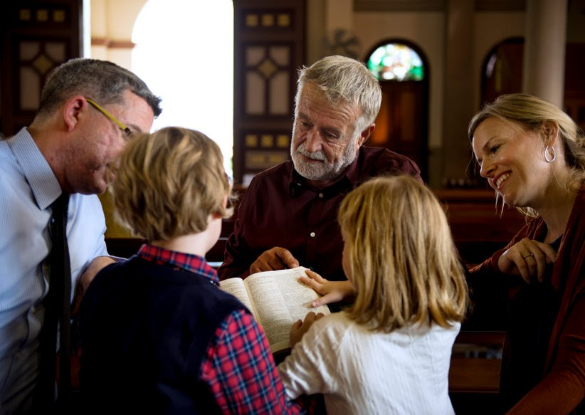 An older man giving a children's sermon to a family.