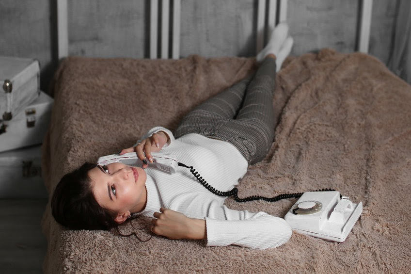 Young woman calling on a corded phone.